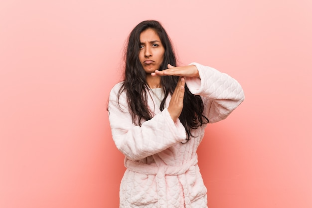 Young indian woman wearing pajama showing a timeout gesture.