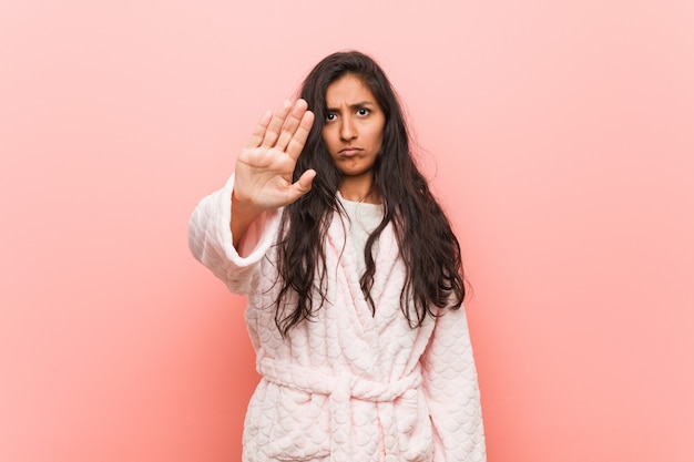 Young indian woman wearing pajama standing with outstretched hand showing stop sign, preventing you.
