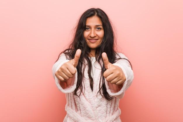 親指を立ててパジャマを着て、何かを応援し、コンセプトをサポートし、尊重する若いインド人女性。