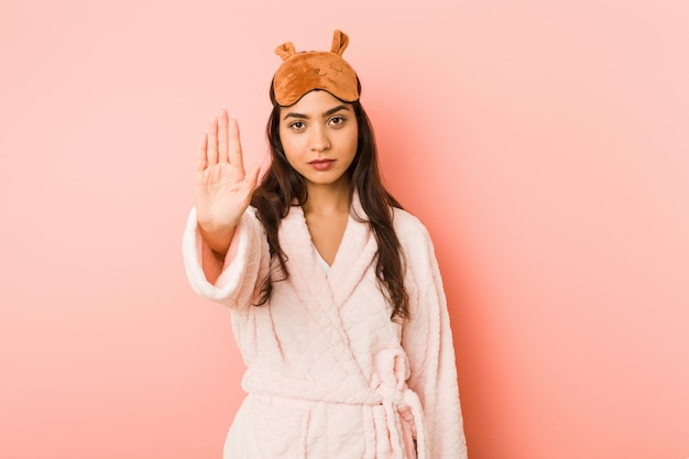 Young indian woman wearing a pajamas and sleep mask standing with outstretched hand showing stop sign, preventing you.