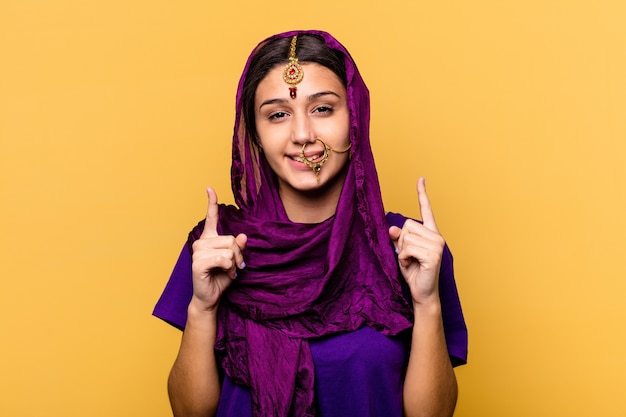Young indian woman wearing a traditional sari clothes isolated on yellow background indicates with both fore fingers up showing a blank space.