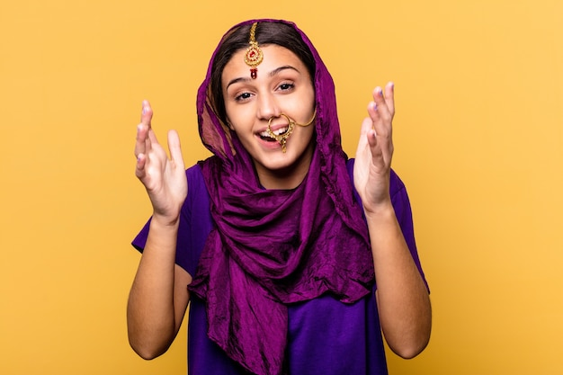Young indian woman wearing a traditional sari clothes isolated on yellow background receiving a pleasant surprise, excited and raising hands.