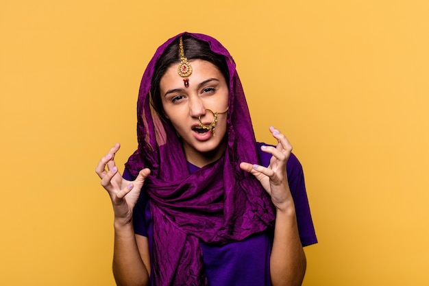 Young indian woman wearing a traditional sari clothes isolated on yellow background upset screaming with tense hands.