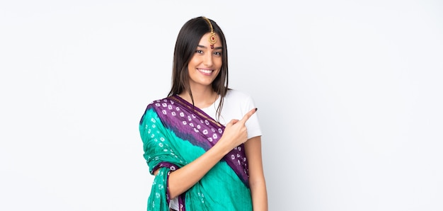 Young indian woman on white wall pointing to the side