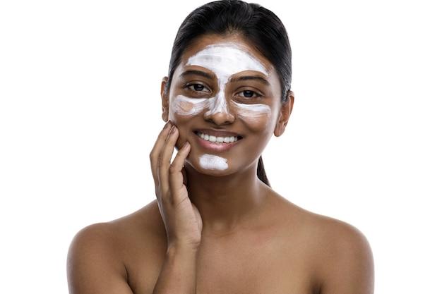 クレンジングマスクを顔に塗った若いインド人女性。白で隔離。