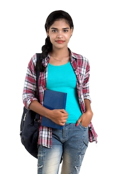 Молодая индийская женщина с рюкзаком стоя и держа тетради, позируя на белой стене.
