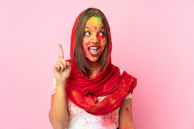 Young indian woman with colorful holi powders on her face isolated on pink wall intending to realizes the solution while lifting a finger up