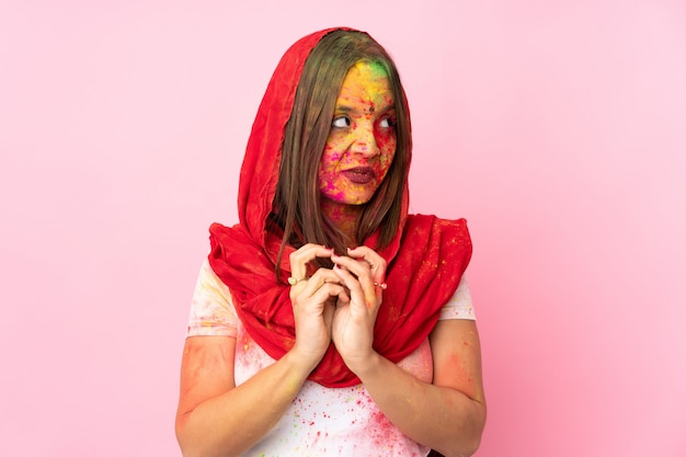 Young indian woman with colorful holi powders on her face isolated on pink wall scheming something