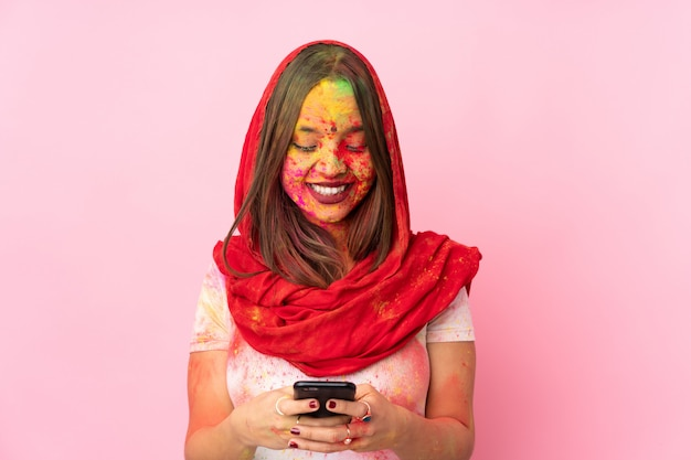 Young indian woman with colorful holi powders on her face isolated on pink wall sending a message with the mobile