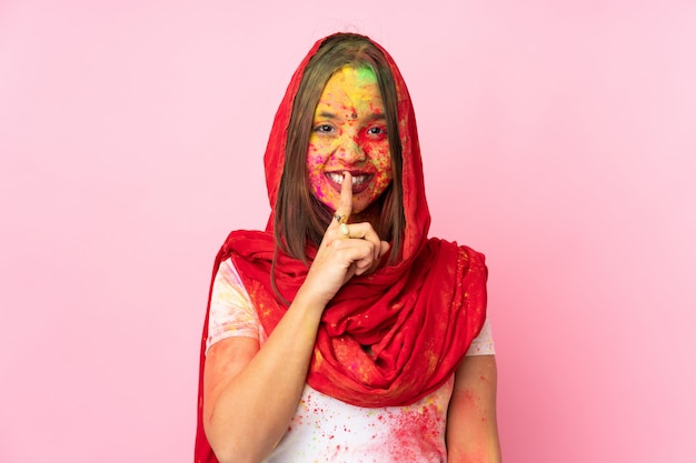 Young indian woman with colorful holi powders on her face isolated on pink wall showing a sign of silence gesture putting finger in mouth