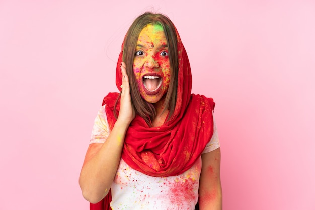 Young indian woman with colorful holi powders on her face isolated on pink wall with surprise and shocked facial expression