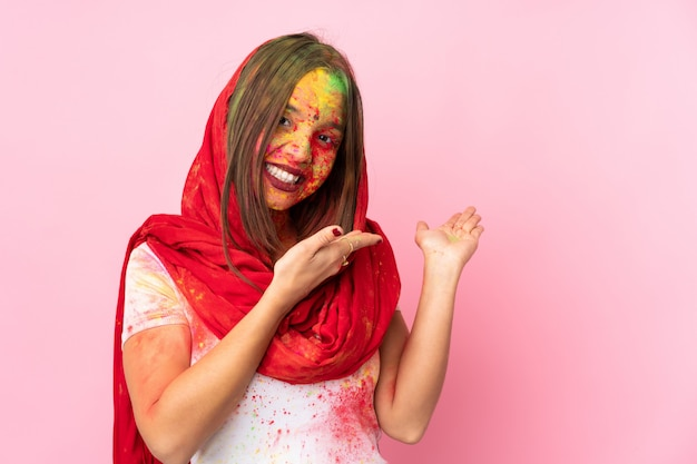 Young indian woman with colorful holi powders on her face on pink wall extending hands to the side for inviting to come