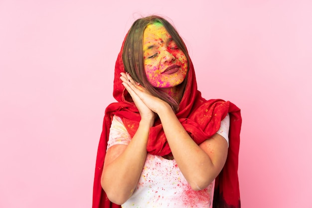Young indian woman with colorful holi powders on her face on pink wall making sleep gesture in dorable expression
