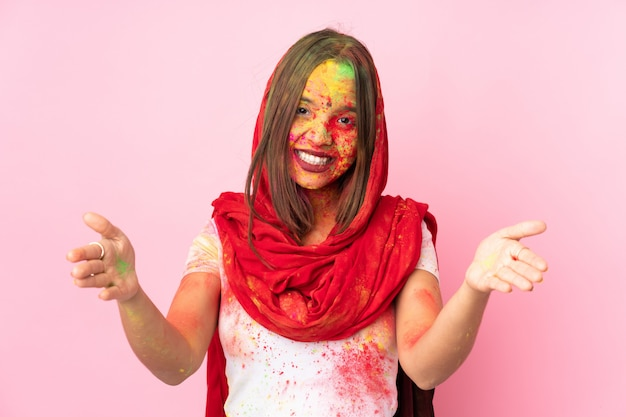 Young indian woman with colorful holi powders on her face on pink wall presenting and inviting to come with hand