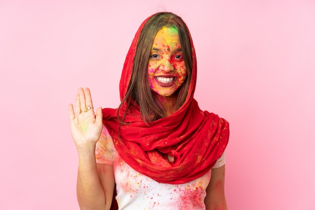 Young indian woman with colorful holi powders on her face on pink wall saluting with hand with happy expression