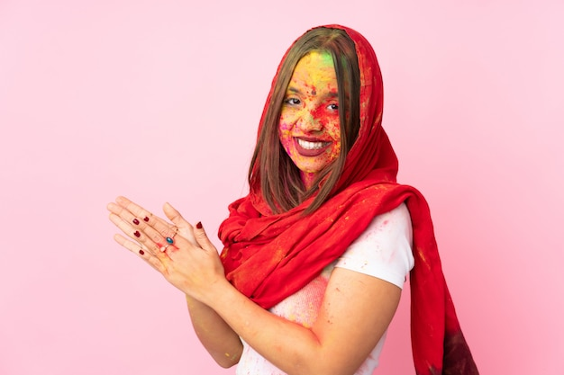 Young indian woman with colorful holi powders on her face on pink wall scheming something