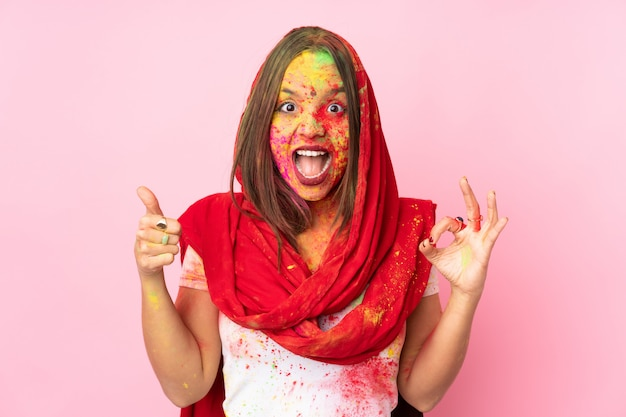 Young indian woman with colorful holi powders on her face on pink wall showing ok sign and thumb up gesture
