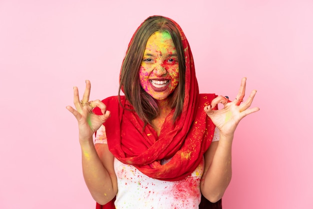 Young indian woman with colorful holi powders on her face on pink wall showing ok sign with two hands