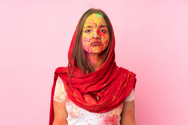 Young indian woman with colorful holi powders on her face on pink wall with sad expression