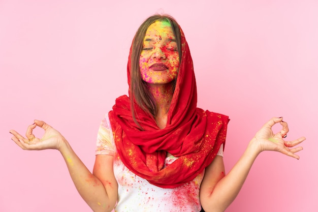 Young indian woman with colorful holi powders on her face on pink wall in zen pose