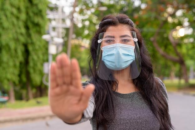 屋外の停止ジェスチャーを示すマスクと顔のシールドを持つ若いインド人女性