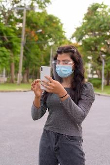 Молодая индийская женщина с маской и щитком для лица разговаривает по телефону в парке на открытом воздухе