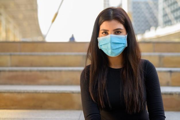Молодая индийская женщина с маской для защиты от вспышки вируса короны на лестнице в городе