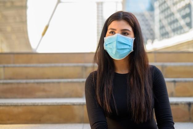 Молодая индийская женщина с маской для защиты от вспышки вируса короны думает на лестнице в городе