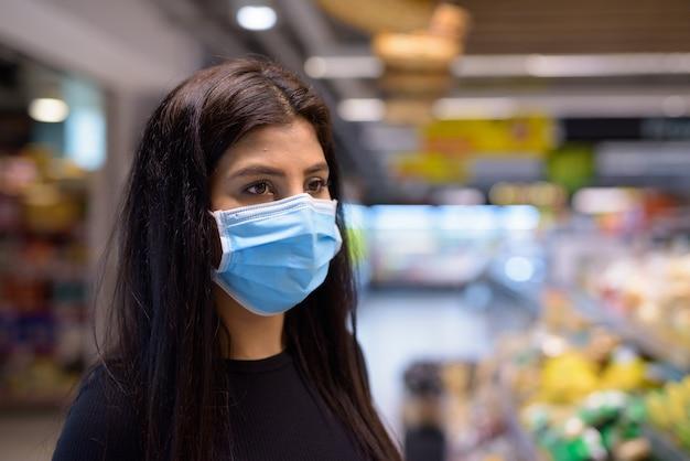 Молодая индийская женщина с маской, делающей покупки на расстоянии в супермаркете