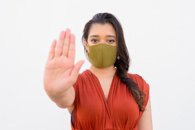 Молодая индийская женщина с маской, показывая стоп жест на белом фоне