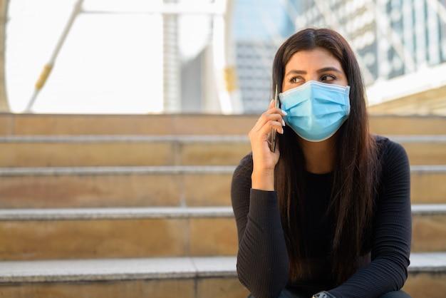 Молодая индийская женщина с маской разговаривает по телефону и сидит у лестницы в городе