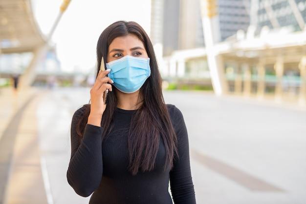 마스크 스카이 워크 다리에서 전화 통화와 젊은 인도 여성