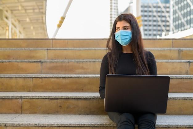 Молодая индийская женщина с маской думает, используя ноутбук и сидя у лестницы в городе