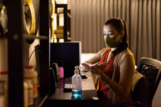 Young indian woman with mask using hand sanitizer and rubbing hands together while working from home at night