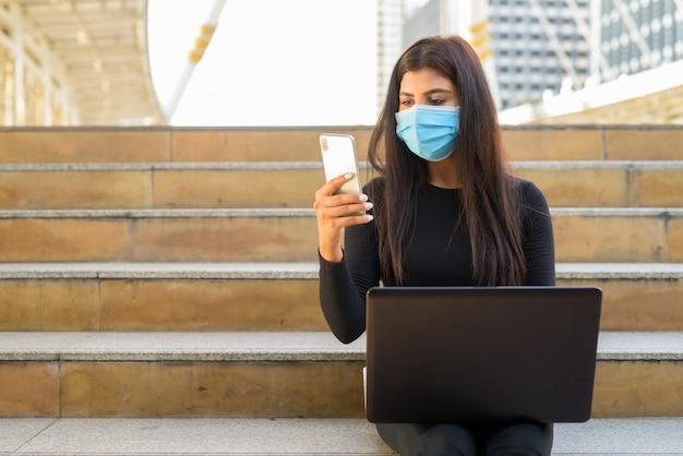 Молодая индийская женщина с маской, используя ноутбук и телефон у лестницы в городе