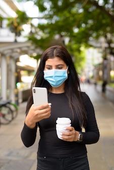 Молодая индийская женщина в маске пользуется телефоном и пьет кофе в дороге, что стало новой нормой во время covid-19 в городе