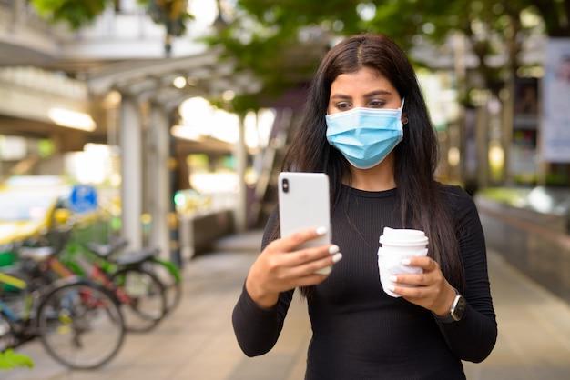 電話を使用して、街でcovid-19中に新しい通常として外出先でコーヒーを飲んでいるマスクを持つ若いインド人女性