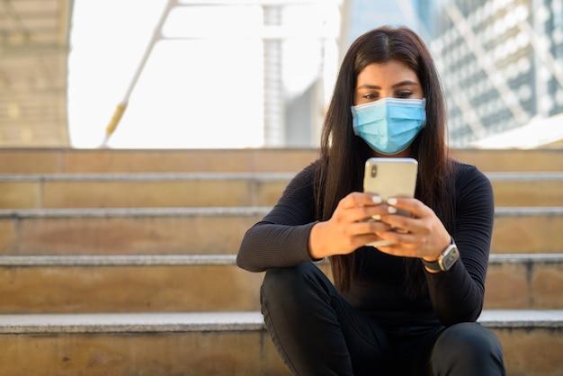 Молодая индийская женщина с маской с помощью телефона и сидя у лестницы в городе
