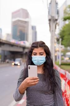 Молодая индийская женщина с маской разговаривает по телефону на улицах города на открытом воздухе