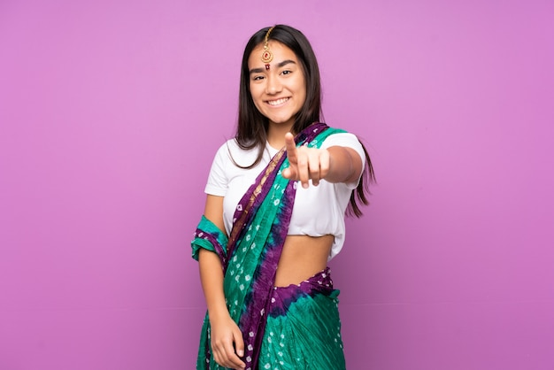 Young indian woman with sari over isolated wall points finger at you with a confident expression
