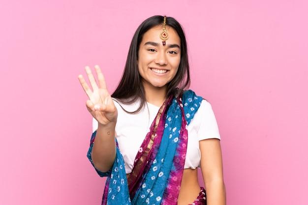 孤立した幸せと指で3を数える上にサリーを持つ若いインドの女性