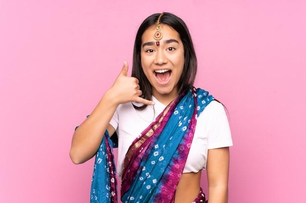 電話のジェスチャーを作る孤立した上のサリーを持つ若いインドの女性。コールバックサイン