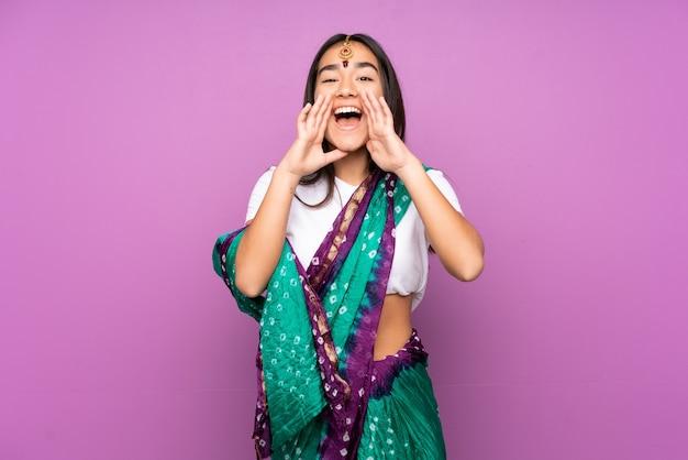 孤立した叫びと何かを発表するサリーを持つ若いインドの女性