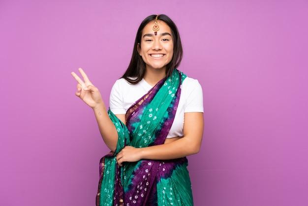 孤立した笑顔と勝利の兆候を示すサリーと若いインドの女性