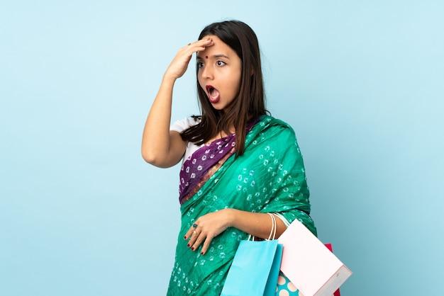 側を見ながら驚きのジェスチャーをしている買い物袋を持つ若いインド人女性