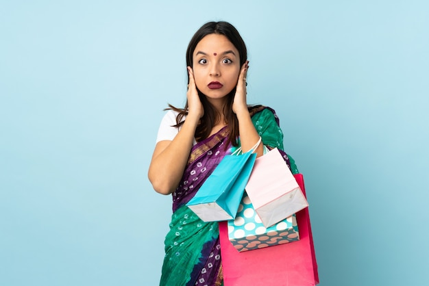 Young indian woman with shopping bags frustrated and covering ears