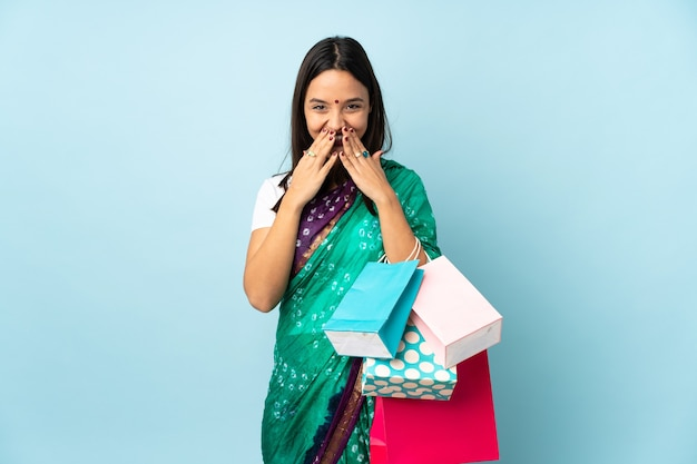 Young indian woman with shopping bags happy and smiling covering mouth with hands
