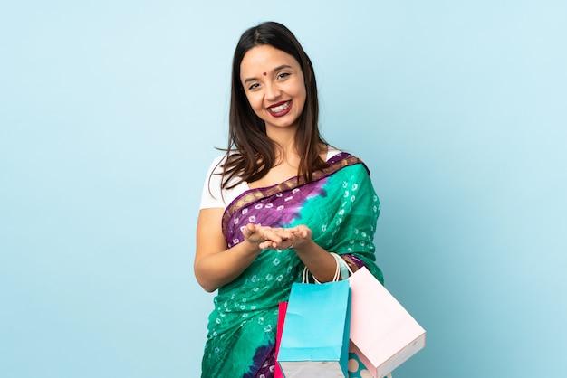 広告を挿入する手のひらに架空の空白スペースを保持している買い物袋を持つ若いインド人女性