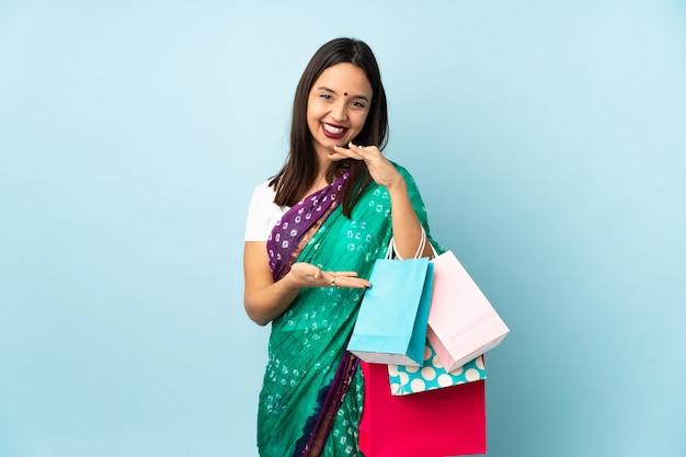 手のひらに空白のスペースを保持している買い物袋を持つ若いインド人女性