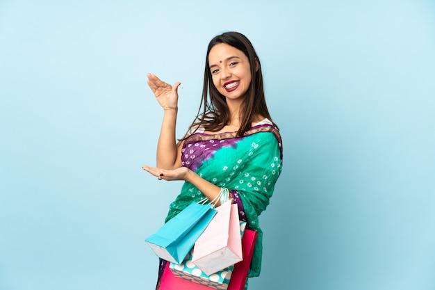 空白を保持している買い物袋を持つ若いインド人女性